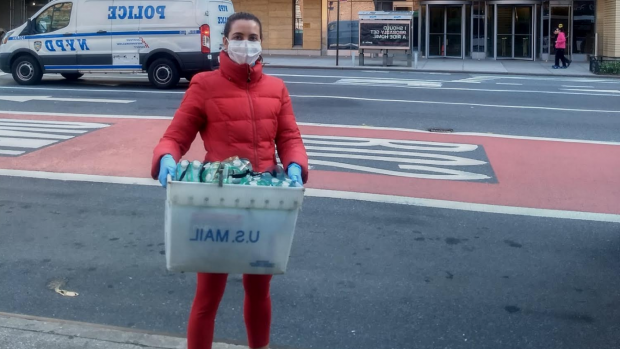 a student wearing a facemask holding a bin of PPE to donate to hospital