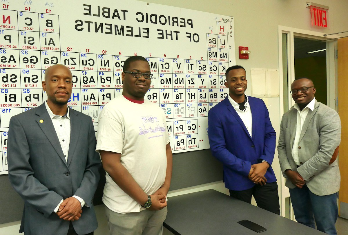 black male students standing in front of periodic table